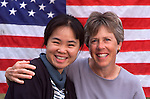 portrait of two smiling women in front of American flag (DEPICTION OR IMPLICATION AS A LESBIAN COUPLE IS STRICTLY PROHIBITED)