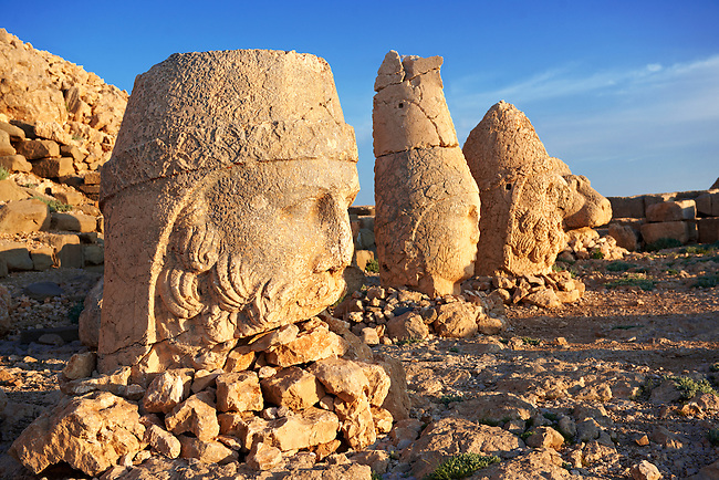 Image of the statues of around the tomb of Commagene King Antochus 1 on the top of Mount Nemrut, Turkey. Stock photos & Photo art prints. In 62 BC, King Antiochus I Theos of Commagene built on the mountain top a tomb-sanctuary flanked by huge statues (8–9 m/26–30 ft high) of himself, two lions, two eagles and various Greek, Armenian, and Iranian gods. The photos show the broken statues on the  2,134 m (7,001 ft)  mountain. 5