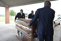 """5/30/15 Indianola, MS.  Fans wait in the rain to see B. B Kings final home coming funeral procession outside the BB King Museum. A family member reaches out to touch the casket for one last time at the gravesite of Mr. King during the burial outside in the rain. The Thrill is gone, the casket holding the body of BB King arrives at the Bell Grove Missionary Baptist Church for his final homecoming. Blues legend B.B. King is is laid to rest in the shadow of the cotton gin at the B.B. King Museum and Interpretive Center. Mr King's final homecoming procession included a black horse WITH A saddle flanked with two of BB's famous """"Lucielle"""" guitars signed by Mr. King. Fans lined the streets to watch the procession and pay their respect to the King of the Blues. Photo ©Suzi Altman"""