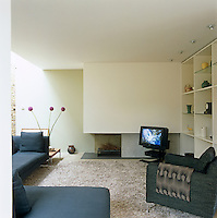 The contemporary living room has been furnished with Italian sofas and a shag-pile carpet while one wall has been left as exposed brick