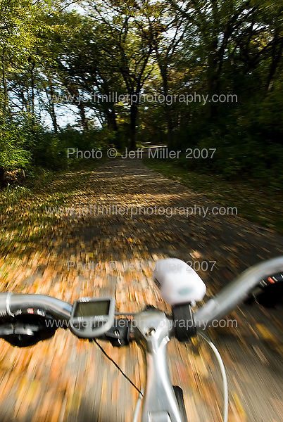 Fallen leaves and trees blur past as a bicycle passes along the Capital City bike trail through the southern edge of Madison, Wis., during autumn on Oct. 17, 2007..Photo © Jeff Miller 2007 - all rights reserved.www.jeffmillerphotography.com  ?  608-250-2374.Date: 10/07   File#: NIKON D200 digital camera frame 8757