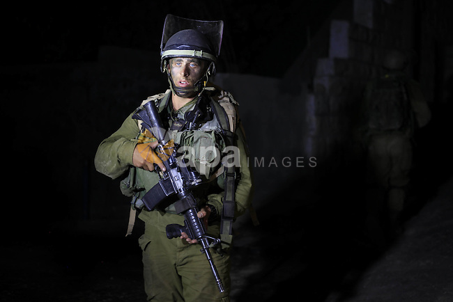 Israeli soldiers patrol on the West Bank village of Aroura near Ramallah, early on June 20, 2014. Israeli authorities have arrested about 300 activists, including 200 members of Hamas, and raided several hundred buildings following the disappearance of three Israeli teenagers last week, according to reports. No organization has claimed responsibility for the disappearance, which Israel blames on Hamas militants. Photo by Issam Rimawi
