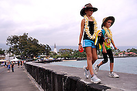 Two sisters (11 years old, 8 years old) wearing Akubra hats and frangipani leis, walking on sea wall. Kailua-Kona, Big Island, Hawaii RIGHTS MANAGED LICENSE AVAILABLE FROM www.PhotoLibrary.com
