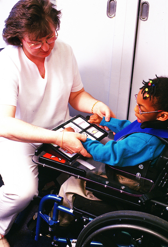 A health care worker helps a child with Cerebral Palsy use an assisted communication sign board.