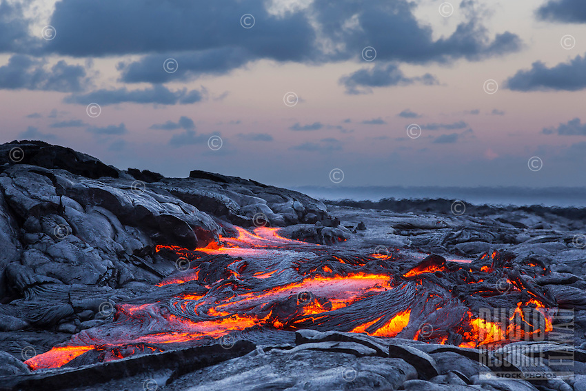Molten lava glowing at dusk in Hawai'i Volcanoes National Park, Hawai'i Island.