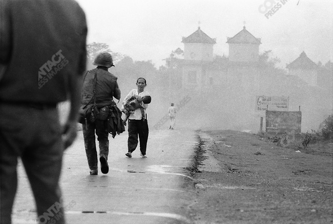 Smoke rises above village pagoda after an accidental napalm bombing of civilians during a battle in Trang Bang. Children and adults burned by the attack run down the road, away from the town, Trang Bang, South Vietnam, June 8, 1972