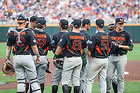 Miami Hurricanes team huddle before their game against the Florida Gators in the NCAA College World Series on June 13, 2015 at TD Ameritrade Park in Omaha, Nebraska. Florida defeated Miami 15-3. (Andrew Woolley/Four Seam Images)