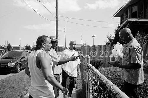 Detroit, Michigan<br /> USA<br /> July 25, 2010<br /> <br /> The Gateway Community Garden has been built and cultivated by Michigan prison inmates finishing their sentences at the Gateway halfway house on East Jefferson Avenue-a main artery in Detroit. They have created a small but vibrant inner-city garden. Using a vacant lot and recycled debris from a demolished house nearby, a dozen or more inmates are growing corn, tomatoes, peppers, watermelons, lettuce and squash.<br /> <br /> The men give away the fruits and vegetables to needy people and appreciate purposeful work to fill their final days of incarceration. Michigan prison inmate Harley Hubble, 50 is one of the principle players in making the garden a reality. He spent three of his 10 year sentence studying horticulture. He learned about crops, soil management, landscape design and greenhouses.<br /> <br /> In this image three inmates hand over freshly picked cucumbers to a neighbor.<br /> <br /> Urban gardening has taken Detroit by storm with so many vacant lots available after thousands of homes have been foreclosed, abandoned and demolished many residents and neighborhoods have turned those plots in to productive land.