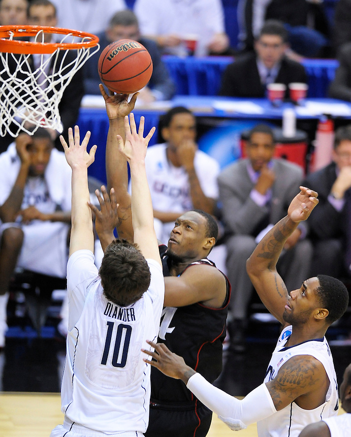 Yancy Gates of the Bearcats gets a bucket over Huskies' Tyler Olander. UConn defeats Cincinnati 69-58 during the 3rd round of the NCAA Tournament at the Verizon Center in Washington, D.C on Saturday, March 19, 2011. Alan P. Santos/DC Sports Box