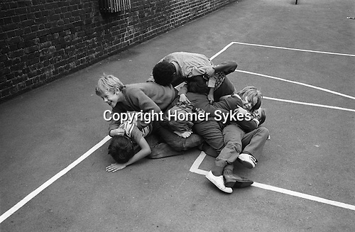 Junior school children boys  play fighting,  playground games. South London. 1970s England. UK..