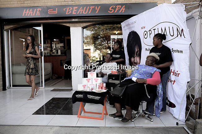 SOWETO, SOUTH AFRICA - MAY 12: Dorah Mtetwa, age 22, an university student walks out of a beauty spa after doing her nails on May 12, 2007 in Soweto, South Africa. Ladies has a free massage in mother's day at an exclusive beauty spot and spa. (Photo by: Per-Anders Pettersson)