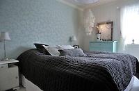 A simple but cosy bedrom, furnished with a mixture of older vintage pieces and new luxury soft furnishings, such as the velvet quilt and cushions