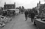 Balsall Heath, Birmingham. 1968<br /> A Tinkers  encampment and temporary scrap car dump on waste ground in Balsall Heath, an inner city slum and red light area.<br /> <br /> Gypsy inner city camp site Balsall Heath Birmingham UK 1968. Men walking towards houses on Emily Street and what might be the junction with Upper Highgate Street. <br /> <br /> These photographs were taken on waste ground bordered to the south by Eyton Croft, or and Upper Highgate Street. Emily Street, Stanhope Street and Conybere St. At the time the area was a slum, with houses in very bad disrepair. The area was 90% caucasian, and was a red light area. All extremely improvised.