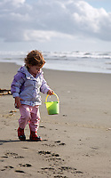 Girl walking on sandy beach with pale, Fort Worden State Park, Port Townsend, Washington, USA