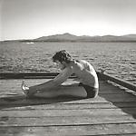 Scan of vintage black & white print. Tolston Wild stretching on old Camp Allagash dock, Moosehead Lake, ME. Negative file # 95-0212-J , 1995