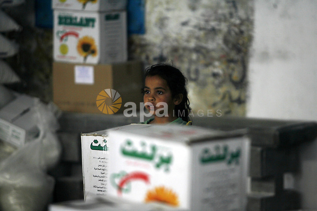 """A Palestinian girl receives monthly food aid from the United Nations Relief and Works Agency (UNRWA) center in the Rafah refugee camp, southern Gaza on May 07, 2012. The UN Agency for Palestinian Refugees (UNRWA) in Gaza launched an appeal for emergency funds to the Palestinian territories of $ 300 million (235 million), The Deputy Chief Commissioner Margo Ellis at the third anniversary of the end of the devastating Israeli operation """"Cast Lead"""" in Gaza (27 December 2008-22 January 2009), said the UNRWA. Photo by Eyad Al Baba"""
