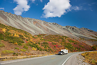 "Motorhome travels the Richardson highway, vibrant fall colors along the Alaska range mountain ridge named ""rainbow mountain"", interior, Alaska."