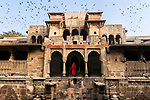 _DSC6340, Vacheron, India, 04/2016, INDIA-13169.  Woman in a red robe entering a building while birds fly above.<br /> <br /> CHECK IMAGE USAGE<br /> <br /> FINAL_Vacheron<br /> <br /> retouched_Sonny Fabbri