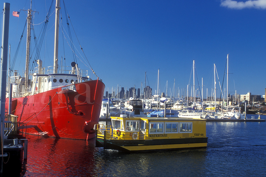 New Jersey, Jersey City, Liberty State Park, A yellow water taxi leaves the dock on Upper New York Bay transporting passengers to Manhattan, New York. A red craft is docked in background.
