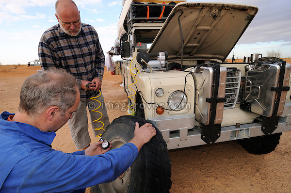 Africa, Tunisia, nr. Tembaine. Siegfried and Wolfgang repairing a flat tyre in the desert on a historic Series 3 Land Rover. --- No releases available, but releases may not be needed for certain uses. Automotive trademarks are the property of the trademark holder, authorization may be needed for some uses.  --- Info: Image belongs to a series of photographs taken on a journey to southern Tunisia in North Africa in October 2010. The trip was undertaken by 10 people driving 5 historic Series Land Rover vehicles from the 1960's and 1970's. Most of the journey's time was spent in the Sahara desert, especially in the area around Douz, Tembaine, Ksar Ghilane on the eastern edge of the Grand Erg Oriental.