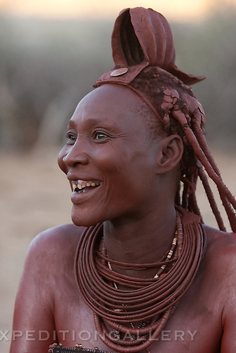 A laughing Himba woman with a traditional leather headress and ochre covered hair braids. Himba women cover their bodies with a traditional mixture of ochre and butter fat giving their skin and hair a reddish coloration. Himba are nomadic herders of goats and cattle, living in the dry desert regions of northwestern Namibia and southern Angola.