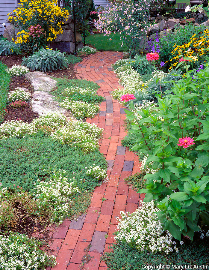 Rockport, Cape Ann, MA<br /> Summer flowers boarder a brick pathway in a Rockport garden