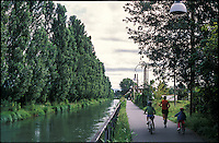 Cernusco sul Naviglio (Milano). Un uomo che corre e due bambini in bicicletta sulla pista ciclabile lungo il Naviglio Martesana --- Cernusco sul Naviglio (Milan). A runner and two kids by bike on the path along the Naviglio Martesana canal