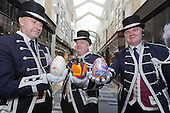 The Beadles of Burlington Arcade, L-R: John Capper, Mark Lord and Kevin McGrory, hold Jesmonite decorated eggs designed by Royal Academians in support of the Royal Academy Schools. They will be auctioned at the Royal Academy Schools Annual Dinner and Auction on 25 March alongside 9 further eggs and other works. The Beadles held the following eggs L-R: Lot 47 by Anthony Green RA, A Floral Kiss, 2014, oil paint; Lot 53 by Bob and Roberta Smith RA Elect, Oval Egg, 2014, acrylic paint and Lot 43 by Eileen Cooper RA, Swirl, 2014, acrylic paint.