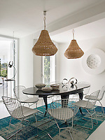 Providing colour and a focal point to the all white dining room is a large turquoise checked rug. On it sits a wooden dining table and wire Harry Bertoia chairs. A pair of large, rattan pendant lights hang above the table
