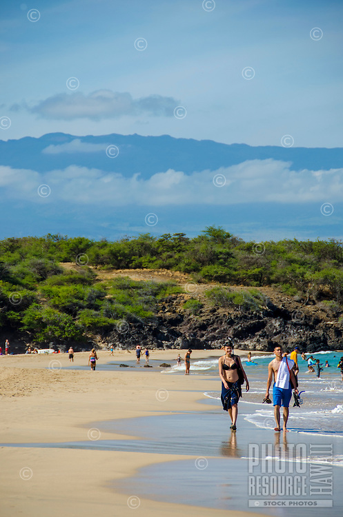 Couple walking at Hapuna Beach, along the Big Island's Kohala Coast, with Hualalai in the distance. This white sand beach has been rated one of the best beaches in the world.