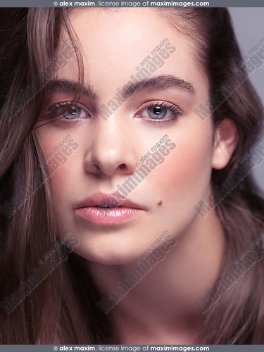 Sensual beauty portrait of a young woman with beautiful gray eyes and long light brown hair