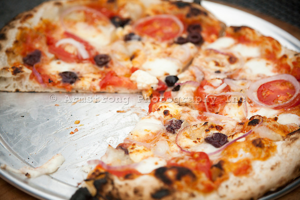 Fresh baked pizza with blistered crust on a pizza pan with one slice removed. Greek-style toppings including tomato slices, red onion, kalamata olives, feta cheese, mozzarella, and tomato sauce.