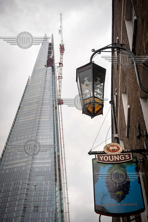 A view of The Shard, which will be the tallest building in Western Europe and is due to be completed and officially inaugurated on the 5th July 2012, opening to the public in 2013. It will contain offices, restaurants, a hotel, apartments and an observation deck. In the foreground is a pub.