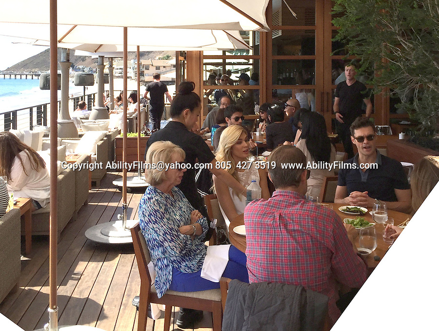 October 18th 2014   Exclusive <br /> <br /> Ryan Seacrest &amp; Shayna Taylor eating lunch at Nobu sushi restaurant on the beach in Malibu California. The couple ate lunch with friends and family. Shayna was wearing a lovely long white lace wedding engagement style dress. <br /> <br /> AbilityFilms@yahoo.com<br /> 805  427 3519 <br /> www.AbilityFilms.com