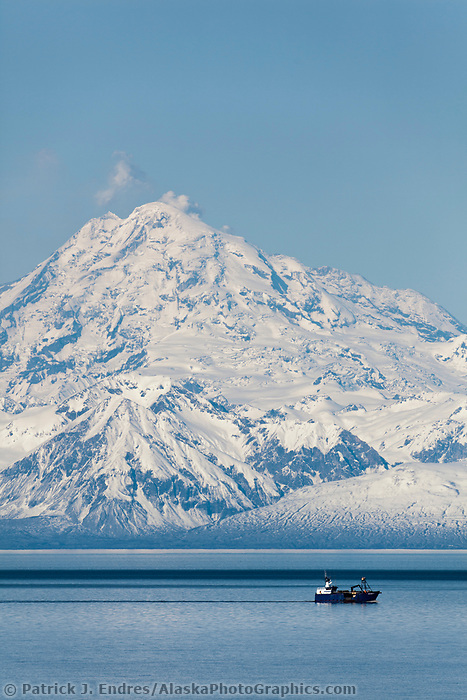 Marine vessel travels through Cook Inlet with Mt. Redoubt, venting gas and vapor, in the distance. Aleutian mountain range, Alaska Peninsula, southcentral, Alaska.