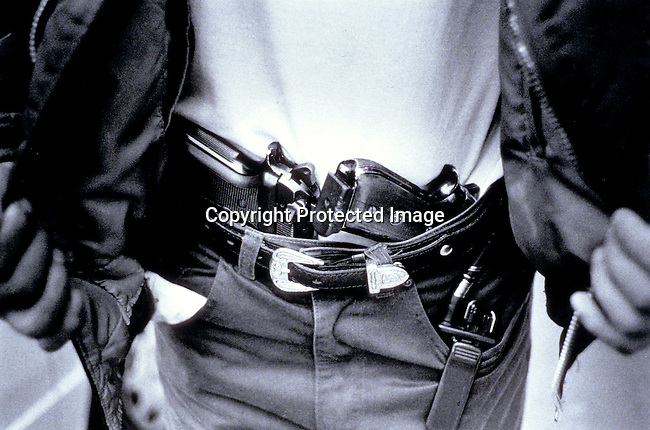 PSPOLIC27122.Police. An undercover police officer on November 22, 1998 showing his arms outside a shop in central Johannesburg, South Africa. A suspected burglar was caught and arrested by the police; guns. .©Per-Anders Pettersson/iAfrika Photos