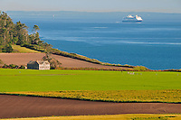 View of historic Ferry House set among farm fields with Puget Sound backdrop and passing Cruiseship. Built by the first white settlers of Whidbey Island and considered the 2nd oldest building in Washington State. Ebey's Landing National Historical Reserve, Whidbey Island, WA. Conserved by the National Park Service.