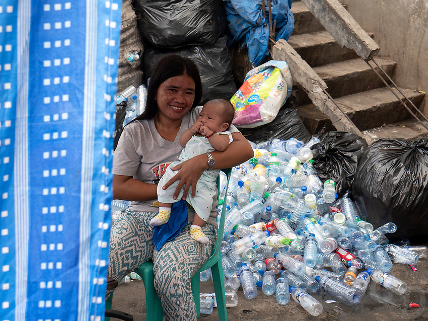 Women and her child amongst collected plastic bottles. Slum area near North Harbour poverty and recycling of plastic, Manila, Philippines