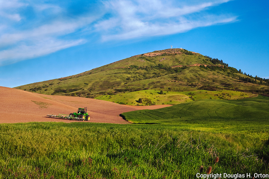A tractor waits near dawn at a farm below Steptoe Butte in the Palouse area of Washington State.  Steptoe Butte is a Washington State Park.