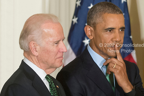 US President Barack Obama (R) and US Vice President Joe Biden (L) attend a reception for St. Patrick's Day in the East Room of the White House, in Washington, DC, USA, 15 March 2016. St. Patrick's Day takes place 17 March.<br /> Credit: Michael Reynolds / Pool via CNP
