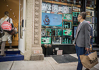 Passer-by hurry past the Wired Store in Soho in New York on Saturday, December 12, 2015. The seasonal store, which features the latest technological gadgets, is ensconced in an interactive window this year, rather than a physical store.(© Richard B. Levine)