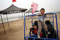 A young boy and girl play in a dune-buggy next to a reservoir that has dropped in level due to a recent drought, in Hebei Province, China.
