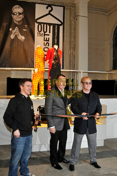 "DAVID FURNISH & ELTON JOHN.Photocall to open pop up shop 'Out The Closet"" selling clothes from Elton John and David Furnish's wardrobes in aid of the Elton John AIDS Foundation, London, England.  .December 11th, 2009.fashion full length sunglasses shades black suit jacket grey gray partner couple trousers cutting ribbon.CAP/PL.©Phil Loftus/Capital Pictures."