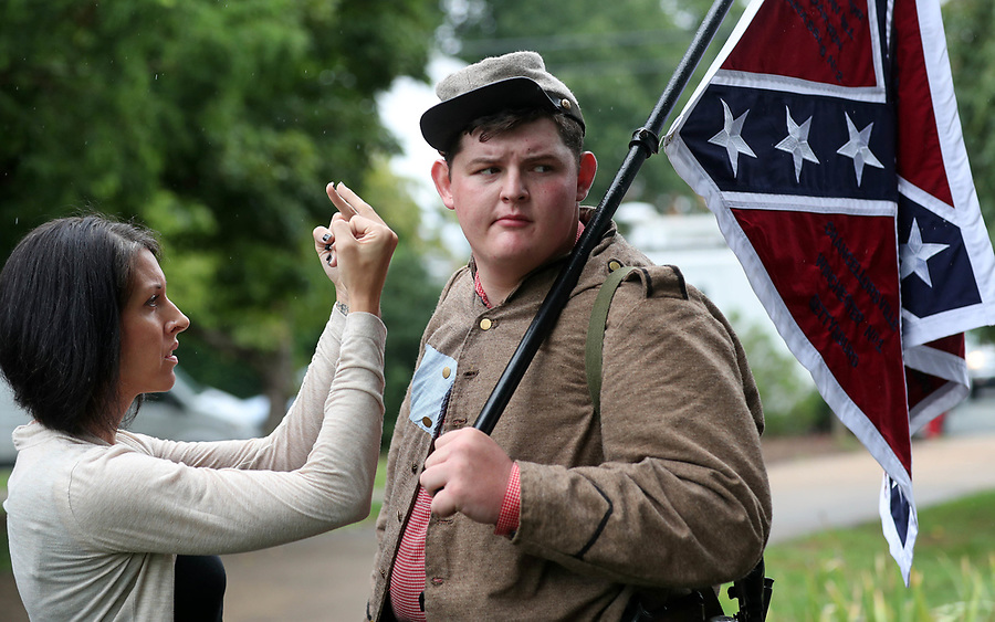 Charlottesville resident Lara Rogers, left, confronts Allen Armentrout of North Carolina who stood wearing a Confederate outfit with 2 guns protecting the Lee Statue Tuesday, Aug. 15, 2017 at Emancipation Park in Charlottesville, Va. A small crowd of Charlottesville residents protested him for 30 minutes before Police escorted Armentrout away from the park. Photo/Andrew Shurtleff