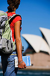 A backpacker looks across Sydney harbour to the Opera House.  Sydney, New South Wales, AUSTRALIA.