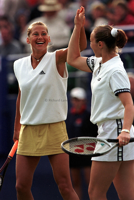Photo. Richard Lane. .International Ladies Tennis, Eastbourne. 19/6/99..Martina Hingis and Anna Kournikova celebrate a point win..