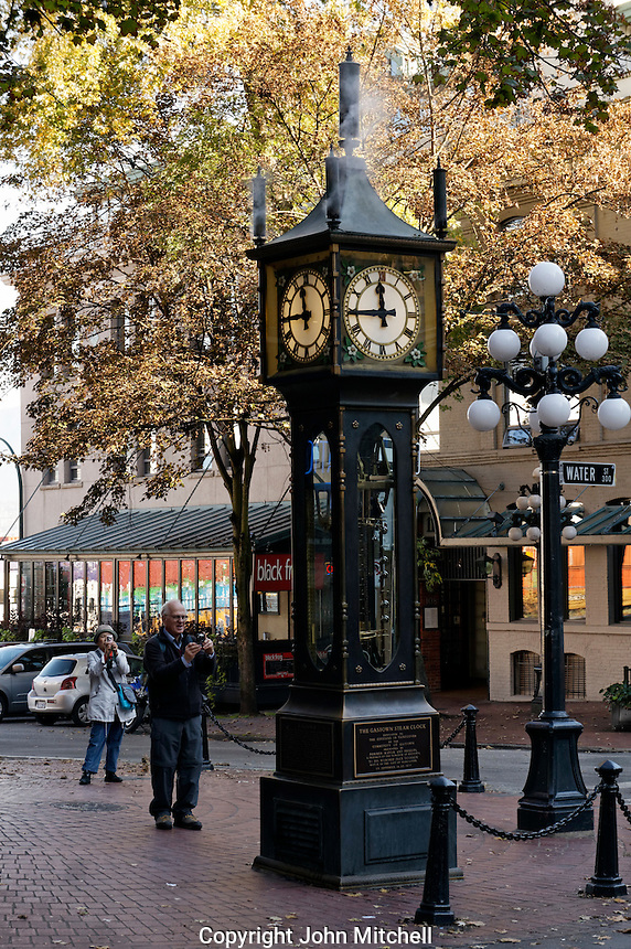 Tourists photographing the Gastown Steam Clock in the historical Gastown district, Vancouver, BC, Canada