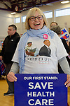 "Westbury, New York, USA. January 15, 2017. NANCY BERGER, of Merrick, is holding an ""OUR FIRST STAND: SAVE HEALTH CARE"" poster and wearing a shirt with President Obama's picture on it, at the ""Our First Stand"" Rally against Republicans repealing the Affordable Care Act, ACA, taking millions of people off health insurance, making massive cuts to Medicaid, and defunding Planned Parenthood."