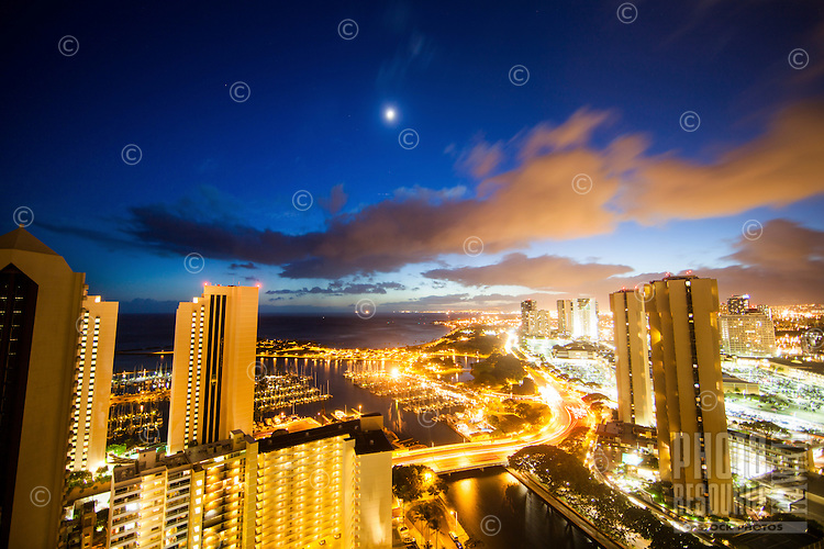 The moon glows over Magic Island and Ala Moana Shopping Center right after sunset on O'ahu.