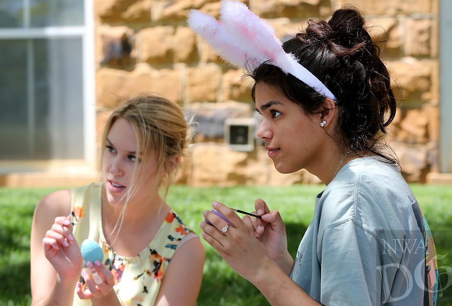 NWA Democrat-Gazette/DAVID GOTTSCHALK  Kimberly Figueroa (right), a junior at the University of Arkansas, paints an egg Wednesday, April 12, 2017, with Ellen Mertes, a sophomore, on the lawn in front of Old Main on the campus in Fayetteville. The University Programs Art Gallery committee hosted Art in the Park giving students the opportunity to create art work. Students were supplied with free canvases, eggs and painting supplies.